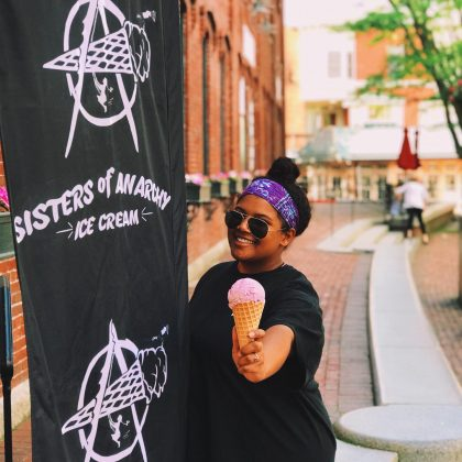 Woman smiling in front of Sisters of Anarchy Ice Cream Flag while holding an ice cream come