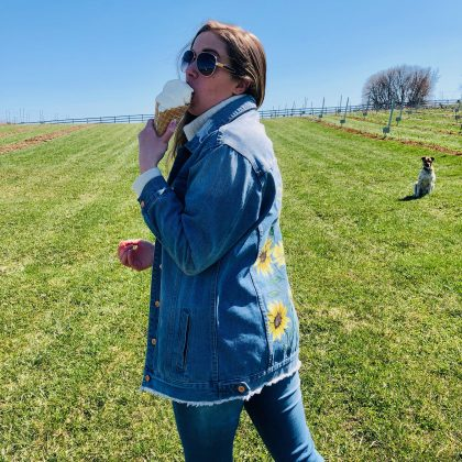 Girl in a jean jacket eating a gluten-free ice cream cone in a field with a dog