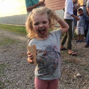 Young girl with curly blonde hair holds an ice cream cone and has chocolate ice cream dripping down her chin