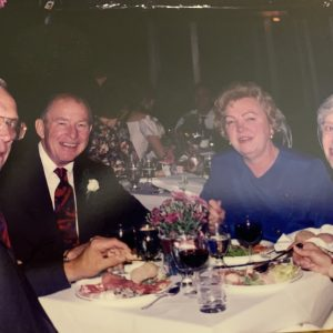 Four older adults sit at a table, from left, two white males next to two white females, all in formal attire