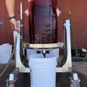 Red berry juice pours out of the sides and out of a spout of a large, round juicer into a white bucket with a red barn backdrop