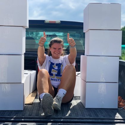 Brunette girl in white t-shits sits in the bed of a blue truck with two thumbs up, surrounded by white packages.