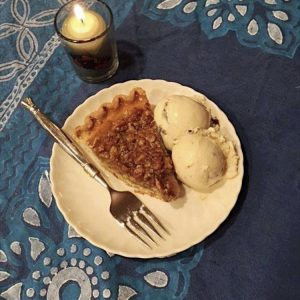 a holiday desert on a blue tablecloth: pecan pie with white ice cream and a tea candle