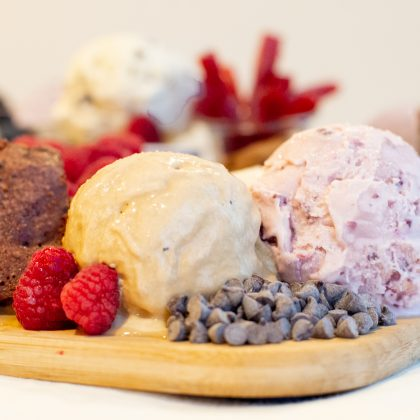 Pogge melting pink and light brown Vermont ice cream sits on a brown cutting board with chocolate chips and red raspberries